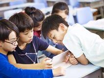 Asiatiska skolbarn som tillsammans använder den digitala minnestavlan royaltyfri fotografi