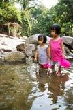 Asiatiska små kinesiska flickor som spelar i liten vik Arkivbild