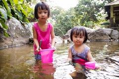 Asiatiska små kinesiska flickor som spelar i liten vik Arkivfoton