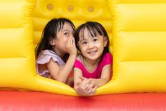 Asiatiska små kinesiska systrar som spelar på den uppblåsbara slotten arkivfoto