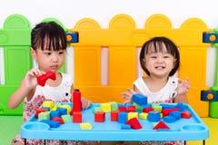 Asiatiska små kinesiska flickor som spelar träkvarter Arkivbild
