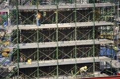 Asiatiska thai arbetare och arbetande byggmästarenybygge för tungt maskineri på höghus för konstruktionsplats i Bangkok, Thailand arkivfoton