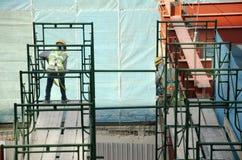 Asiatiska thai arbetare och arbetande byggmästarenybygge för tungt maskineri på höghus för konstruktionsplats i Bangkok, Thailand fotografering för bildbyråer