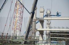 Asiatiska thai arbetare och arbetande byggmästarenybygge för tungt maskineri på höghus för konstruktionsplats i Bangkok, Thailand arkivfoto