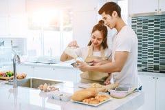 Asiatiska tonåriga par hjälper att göra matställen Arkivbild