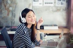 Asiatiska tonårs- flickor lyssnar lyckligt till musik Royaltyfria Bilder