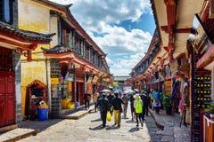 Asiatiska turister går på gatan i den gamla staden av Lijiang Arkivbilder