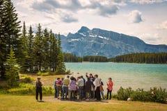 Asiatiska turister som har lunch på sjön för två stålar i den Banff nationen Royaltyfri Fotografi