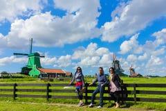 Asiatiska turister som poserar på berömda holländska traditionella väderkvarnar royaltyfri fotografi
