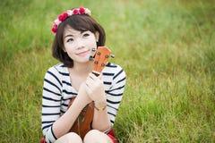 Asiatiska unga kvinnor med ukulelet arkivfoto