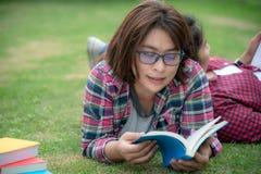 Asiatiska unga kvinnor och vänläsebok på gräs utanför för utbildning royaltyfria bilder
