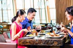 Asiatiska vänner som äter i restaurang Royaltyfri Fotografi