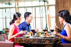 Asiatiska vänner som äter i restaurang Arkivfoto