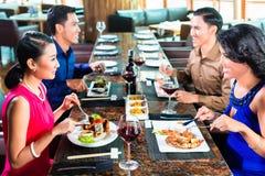 Asiatiska vänner som äter i restaurang Arkivbild