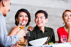 Asiatiska vänner som äter middag i utsmyckad restaurang Arkivfoton