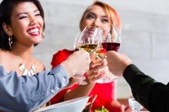 Asiatiska vänner som äter middag i utsmyckad restaurang Arkivbild