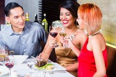 Asiatiska vänner som äter middag i utsmyckad restaurang Arkivbilder