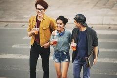 Asiatiska vänner som korsar gatan Arkivfoto