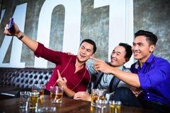 Asiatiska vänner som tar bilder eller selfies i utsmyckad nattklubb Royaltyfri Bild
