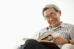 Asiatiskt åldringleende, medan sitta att läsa royaltyfri foto