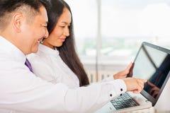 Asiatiskt affärsfolk som använder bärbara datorn på kontoret Arkivfoto