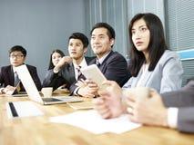 Asiatiskt affärsfolk som i regeringsställning möter arkivfoton