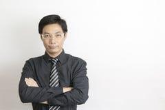 Asiatiskt affärsmananseende på grå bakgrund Royaltyfria Bilder