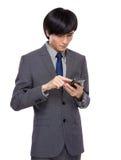 Asiatiskt affärsmanbruk av mobiltelefonen Arkivfoton