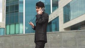 Asiatiskt affärsmanframstickande som talar vid telefonen stock video