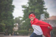 Asiatiskt barn, in i att spela för dräkt för superhero` s arkivfoto