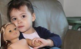 Asiatiskt barn med den Caucasian dockan Arkivfoton
