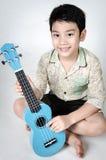 Asiatiskt barn med hans ukulele royaltyfria foton