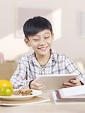 Asiatiskt barn som använder minnestavladatoren Arkivbilder