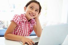 Asiatiskt barn som hemma använder bärbara datorn Arkivfoto