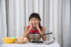 Asiatiskt barn som hemma spelar en kock Royaltyfri Foto