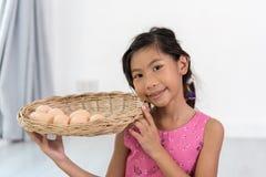 Asiatiskt barn som hemma spelar en kock Arkivbilder