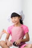 Asiatiskt barn som hemma spelar en kock Arkivfoto