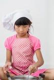 Asiatiskt barn som hemma spelar en kock Arkivfoton