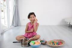 Asiatiskt barn som hemma spelar en kock Royaltyfria Foton