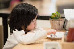 Asiatiskt barn som rymmer en sked och en gaffel med Fotografering för Bildbyråer