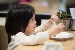 Asiatiskt barn som rymmer en sked och en gaffel med Arkivfoto