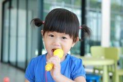 Asiatiskt barn som spelar den plast- mikrofonen på ungerummet fotografering för bildbyråer