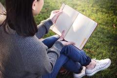 Asiatiskt begrepp för dam Reading Book Park utomhus arkivfoton