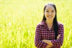 Asiatiskt bondeanseende för ung kvinna i organisk risfält arkivfoton