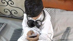 Asiatiskt caucasian pojkebarn för gullig förtjusande liten indier som är upptaget på för smart den bärande headphonen telefonskär stock video