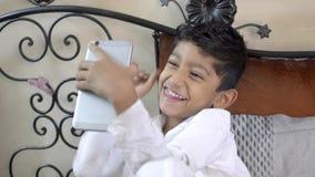 Asiatiskt caucasian pojkebarn för gullig förtjusande liten indier som tar roliga selfies på den roliga mobiltelefonen eller smart