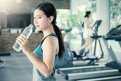 Asiatiskt dricksvatten för ung kvinna efter övning i sportklubba Royaltyfri Bild