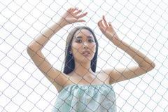 Asiatiskt flickaanseende bak trådstaketet i en bur rymma hennes händer Begrepp fotografering för bildbyråer