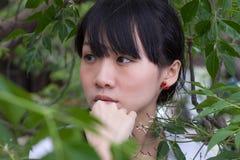 Asiatiskt flickaanseende bland sidor Arkivfoto