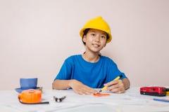 Asiatiskt flickabarn som spelar som en tekniker byggnadsorienteringen Royaltyfri Bild